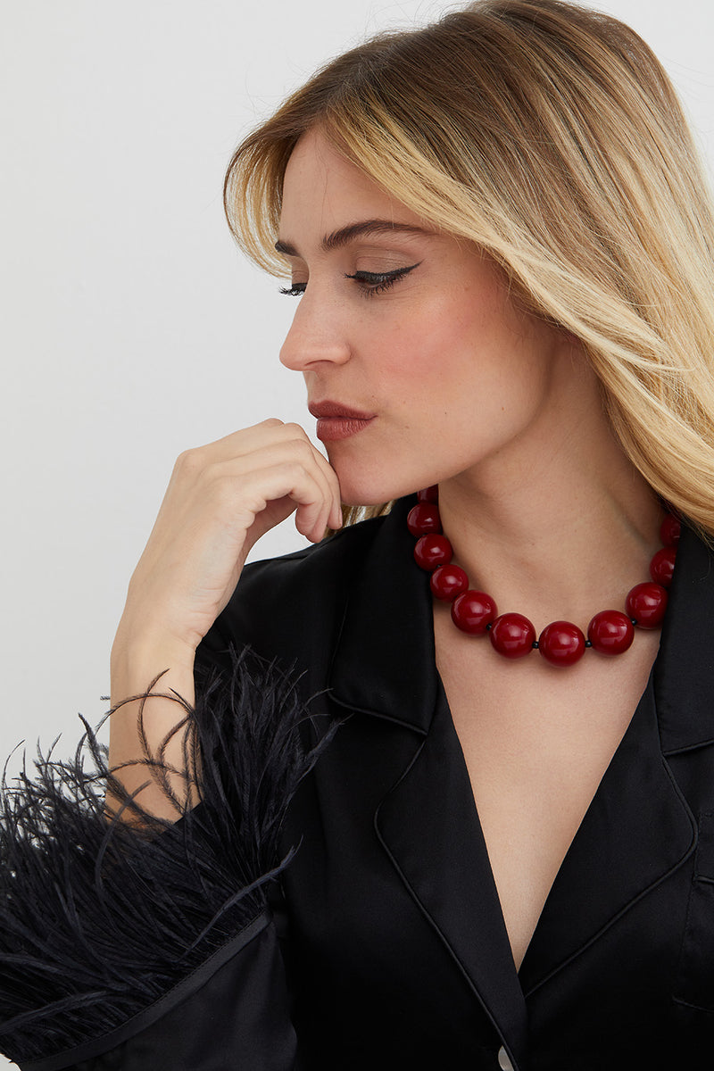 red burgandy choker statement necklace worn by a model in a black top with feathers