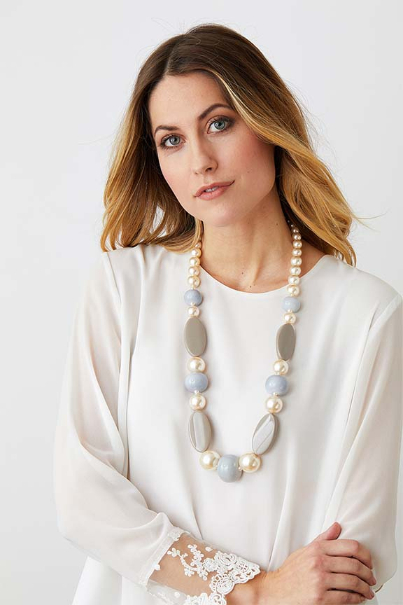 Pearl beige long statement necklace worn by a model in a white lace top