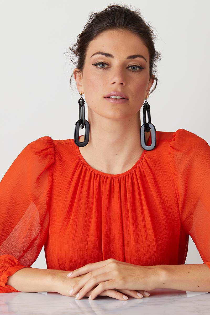 Black chain statement earrings worn by a model in a  red summer dress