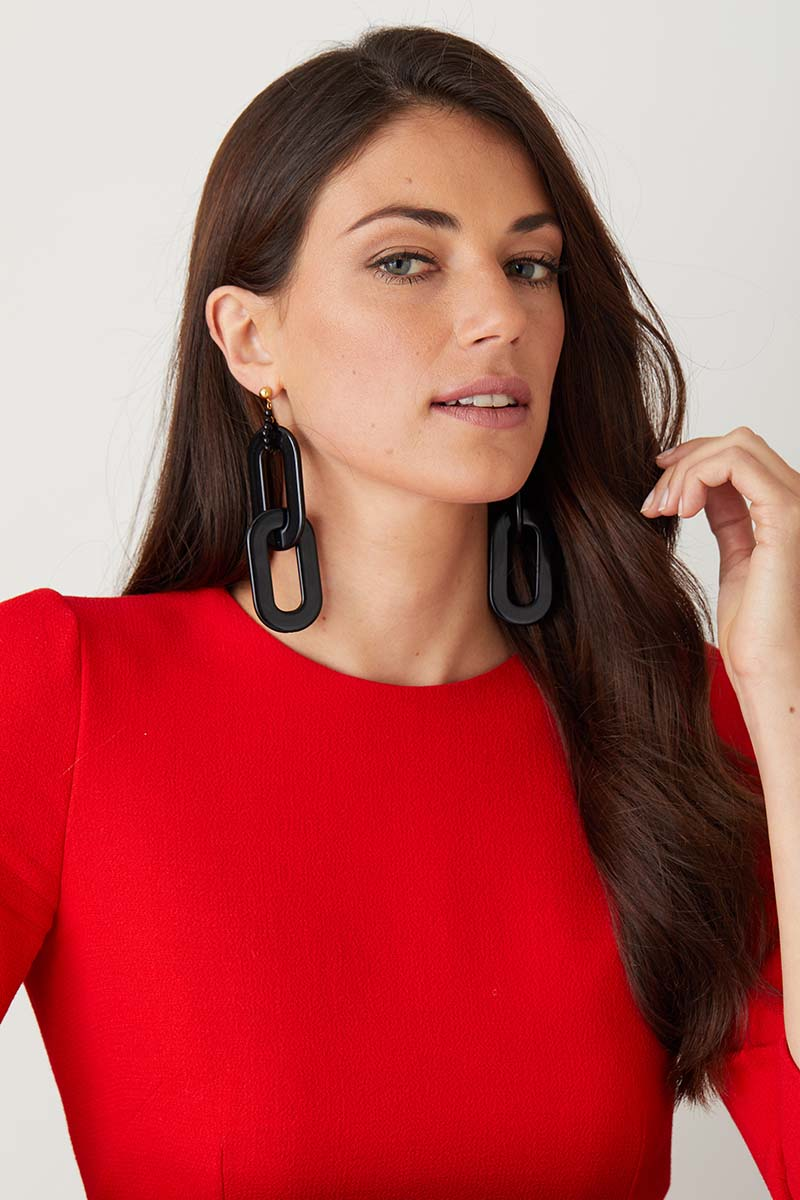 Black chain statement earrings worn by a model in a red dress