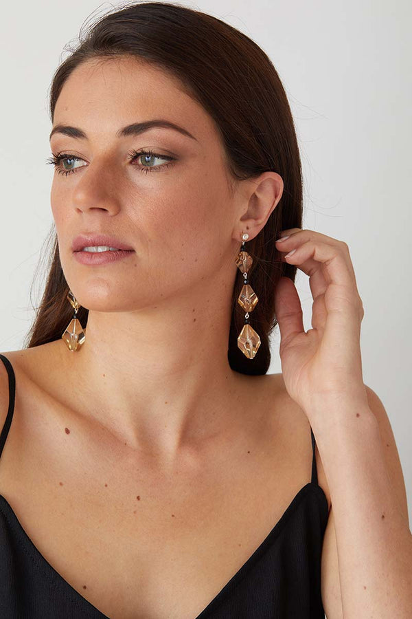 Crystal black statement earrings worn by a model in a black evening dress