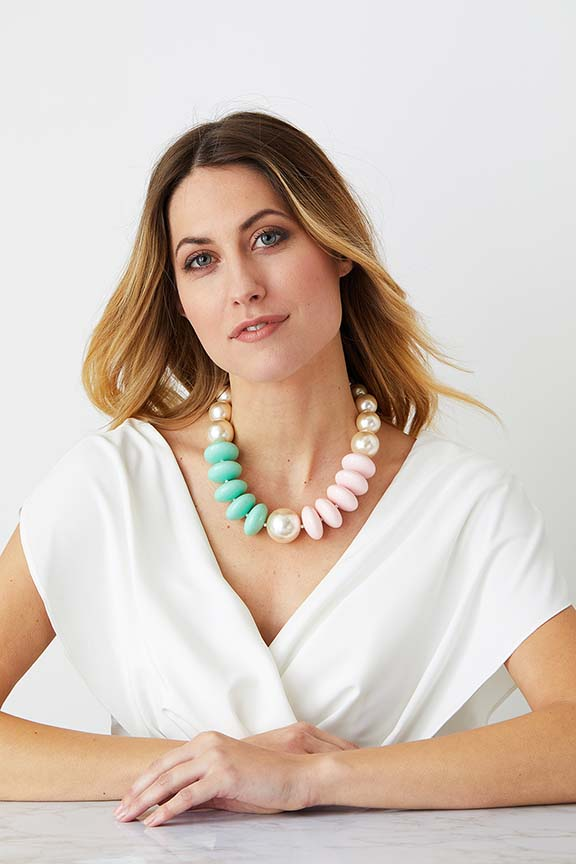 Pearl green pink pastel statement necklace worn by a model in a white elegant dress
