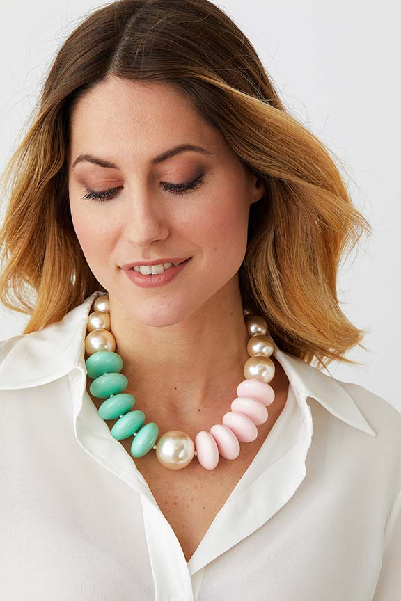 Pearl green pink pastel statement necklace worn by a model in a white collared shirt