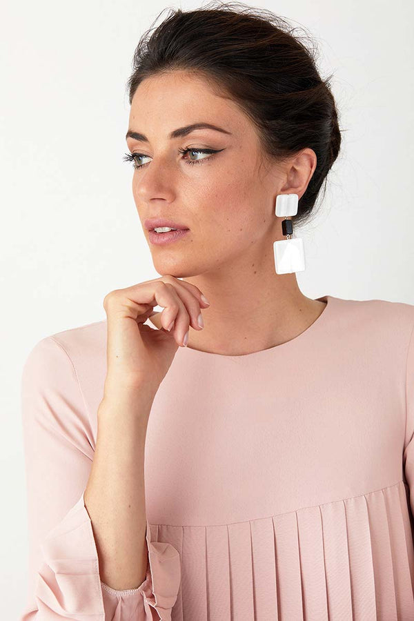 White black statement earrings worn by a model in a pink pleated dress