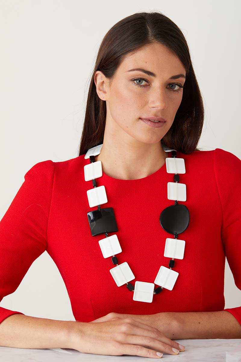 White black statement necklace worn by a model in a red elegant dress