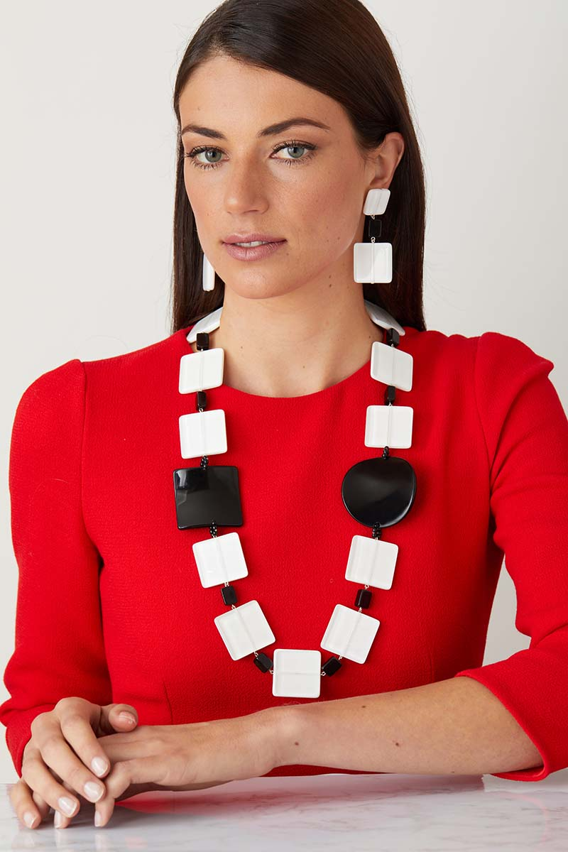 White black statement necklace worn by a model as a pendant set, in a red dress