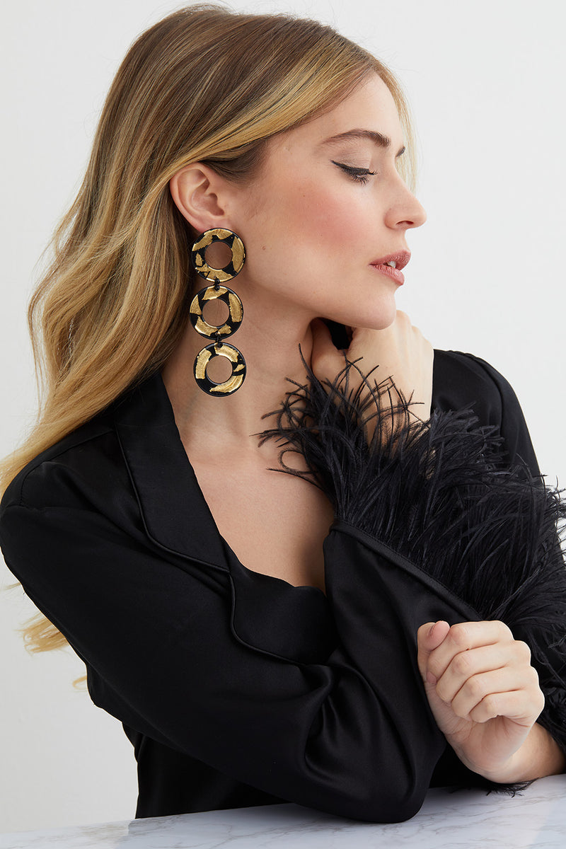 Black and gold triple hoop statement earrings worn by a model in a Lyla Wilde green silk top
