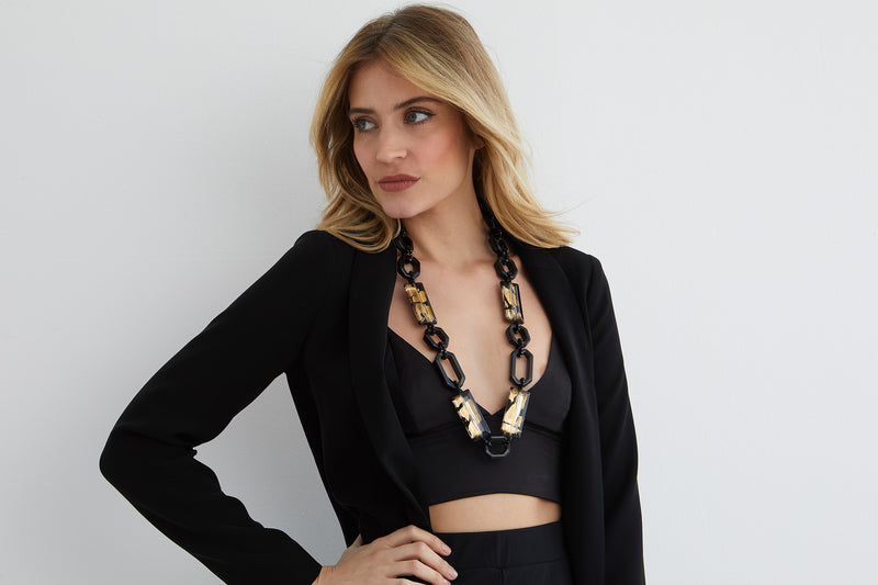 Black and gold chain statement necklace worn by a model in a black crop top