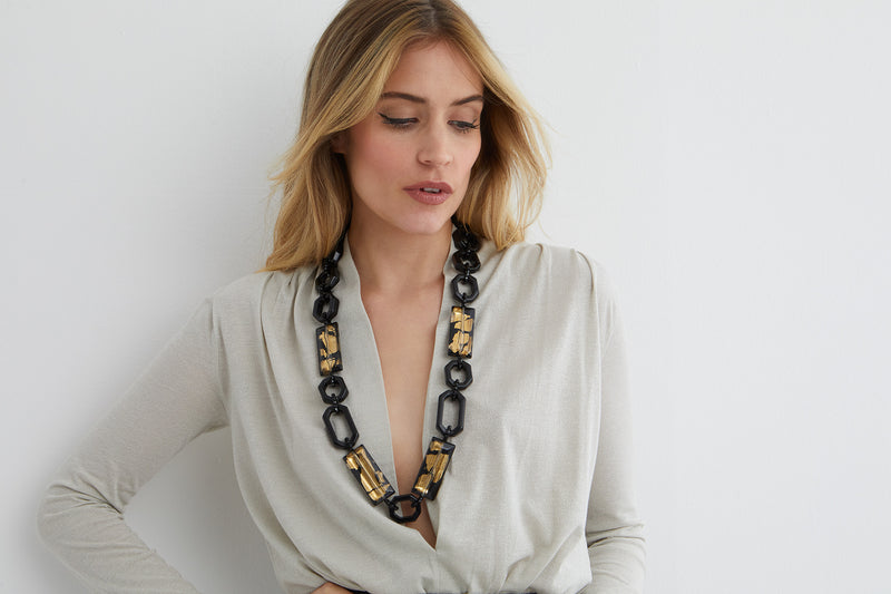 Black and gold chain statement necklace worn by a model in a silver low cut top