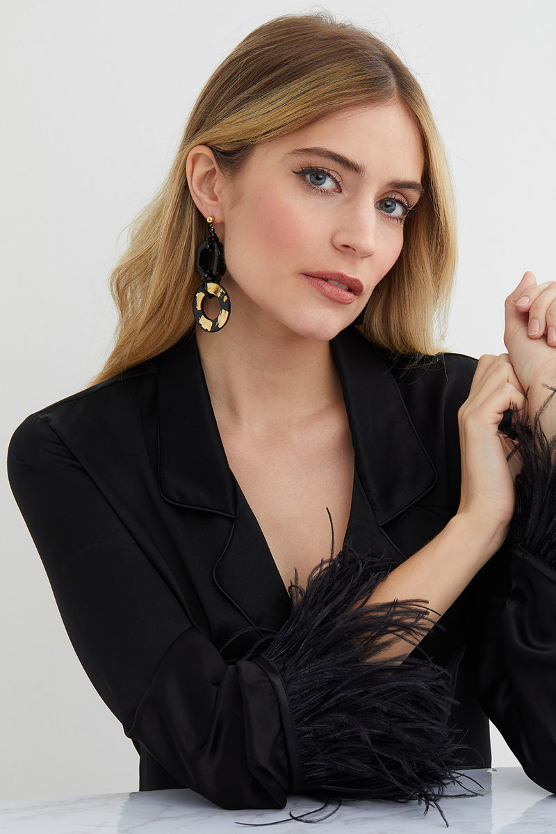 Black and gold hoop statement earrings worn by a model in a black silk feathered top