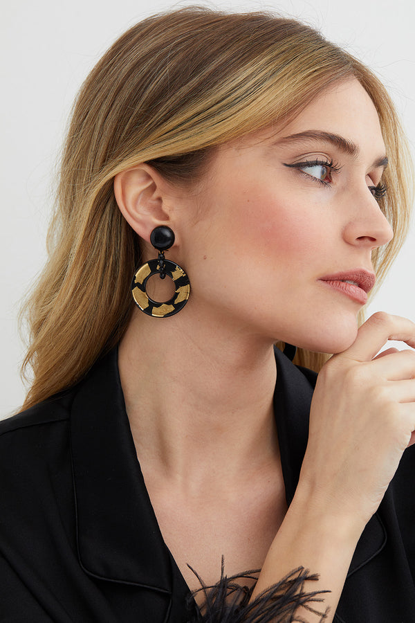 Black and gold hoop statement earrings worn by a model in a Lyla Wilde black silk outfit