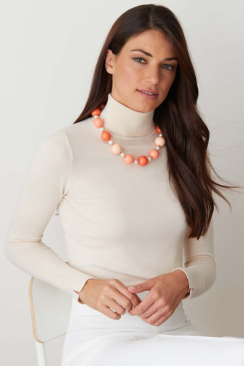 Pink pearl statement necklace worn by a model in a white turtleneck