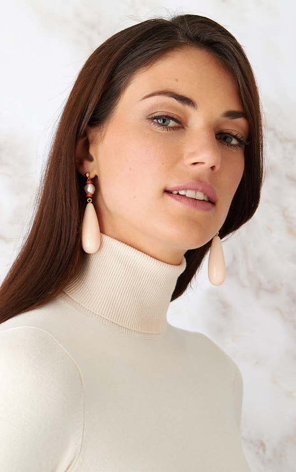 Pink pearl statement earrings worn by a model in a white turtleneck