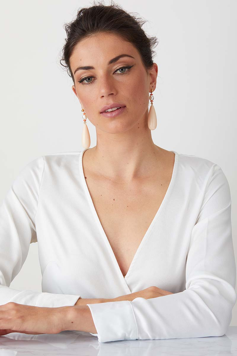 Pink pearl statement earrings worn by a model in a white top