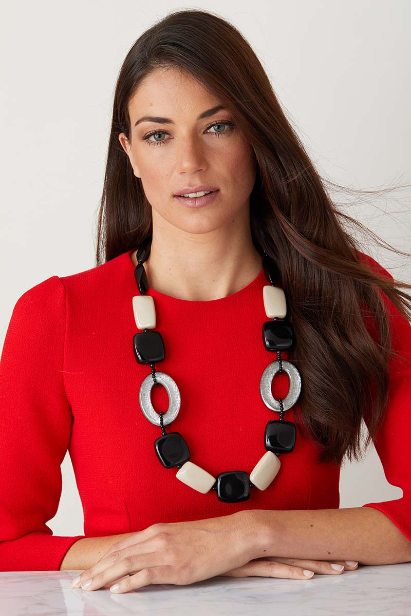 Black beige silver statement necklace worn by a model in a red dress