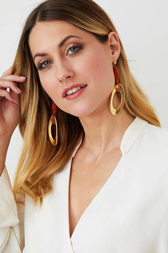Gold amber drop statement earrings worn by a model in a white blazer, made of resin