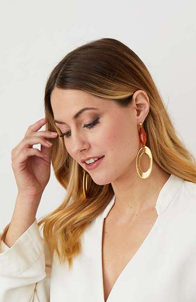 Gold amber drop statement earrings worn by a model in a  white top