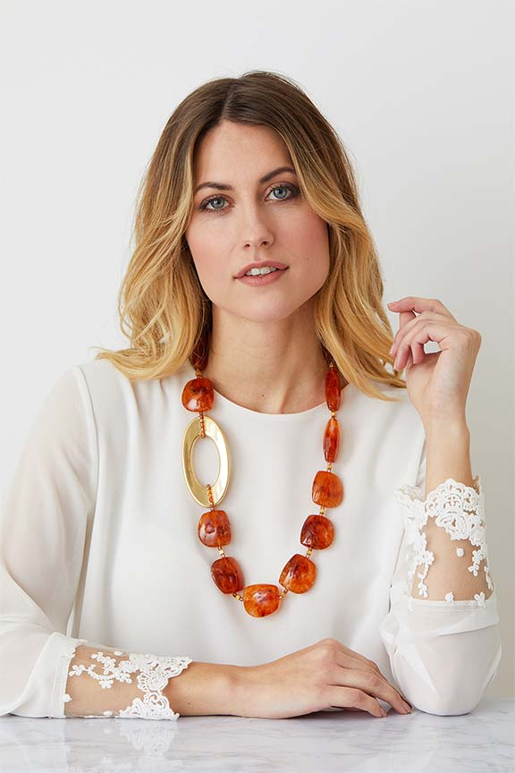 Amber gold statement necklace worn by a model in a lace top