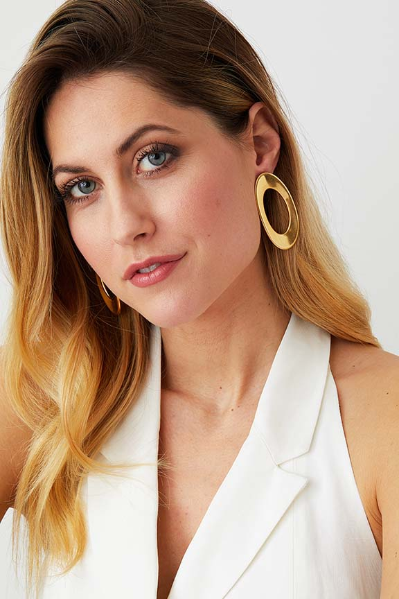 Gold hoop statement earrings worn by a model in a white summer dress
