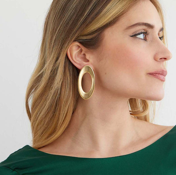 Gold hoop statement earrings worn by a model in a green silk top
