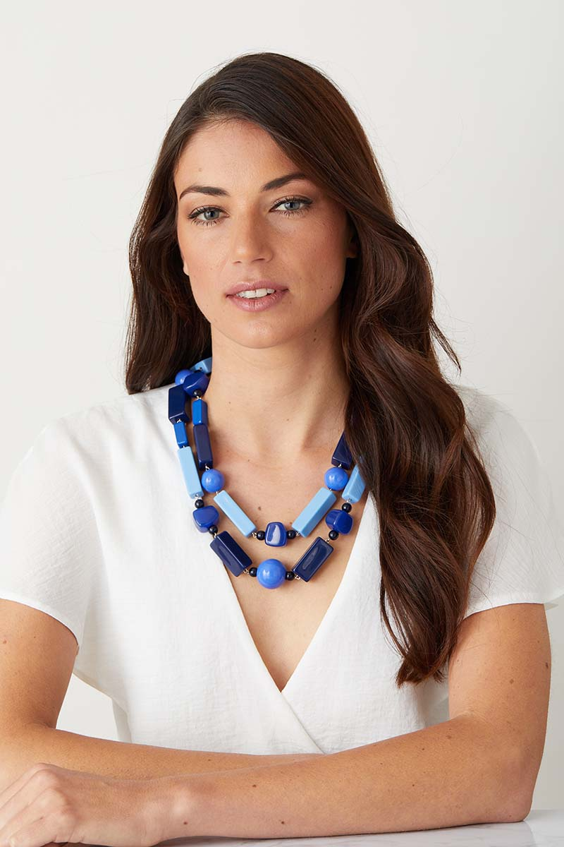 Blue statement necklace worn by a model in a white top