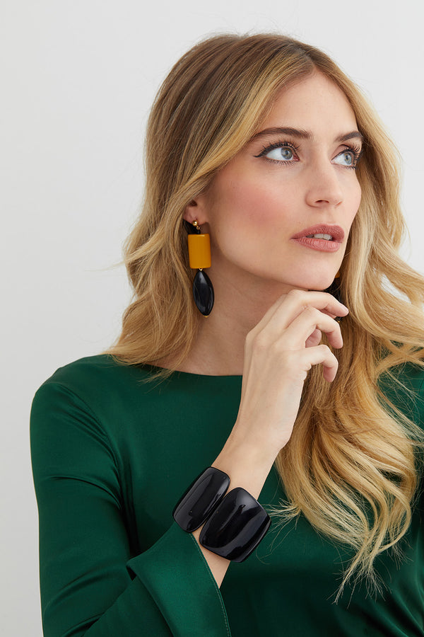 Black and yellow statement earrings worn by a model in a Lyla Wilde green silk top
