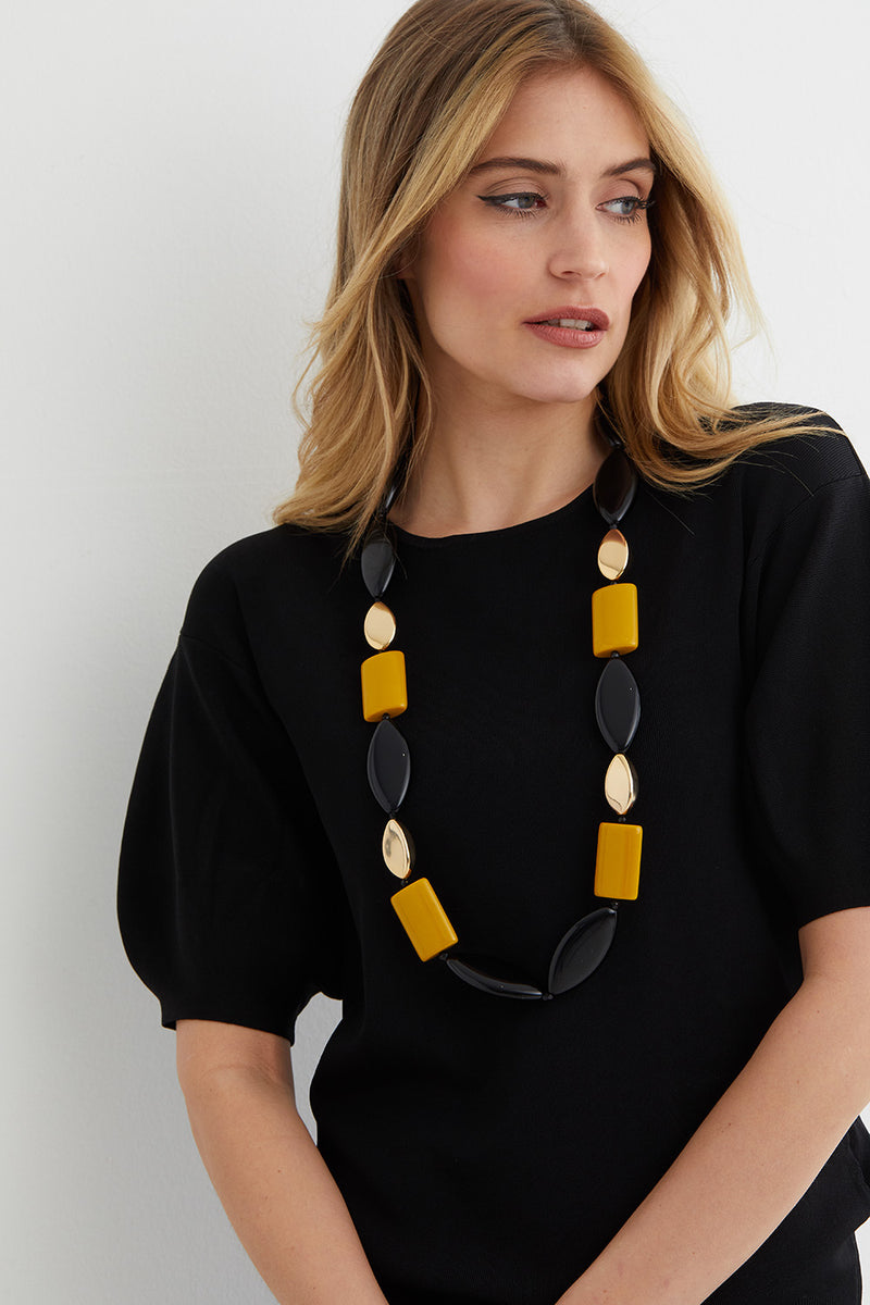 Black yellow gold statement necklace worn by a model in a black top