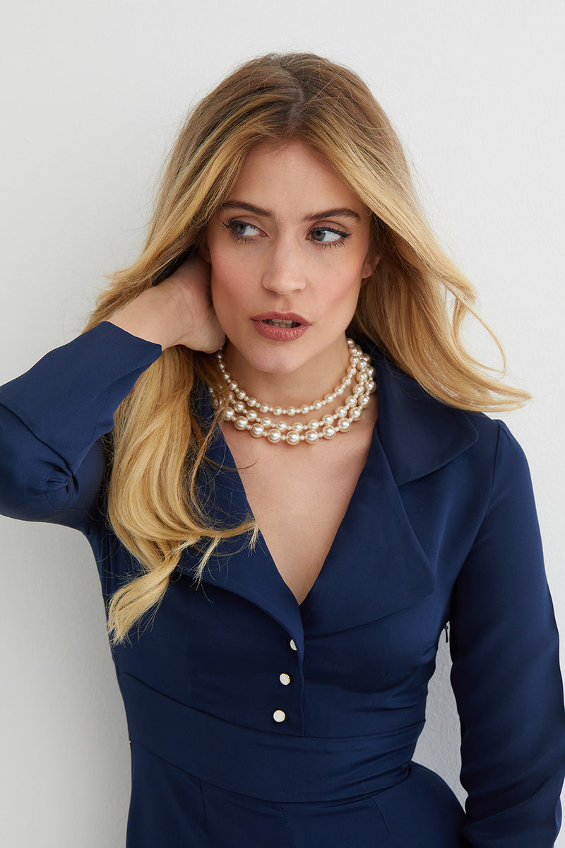 Pearl triple choker statement necklace worn by a model in a blue jumpsuit