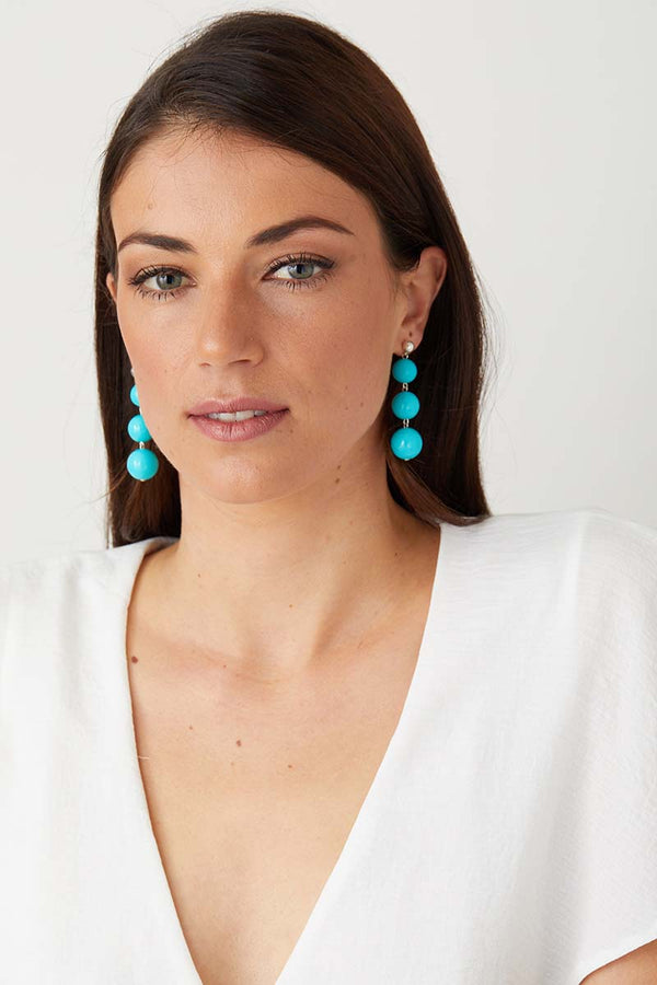 Light blue turquoise statement earrings worn by a girl in a white top