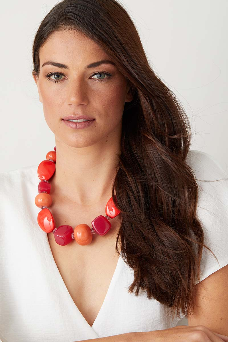 Pink orange red statement necklace worn by a model in a white top
