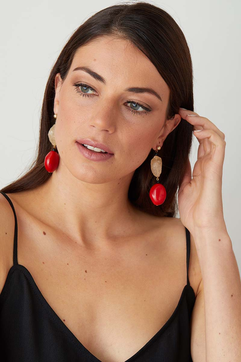 Red coral black statement earrings worn by a model in a black summer dress