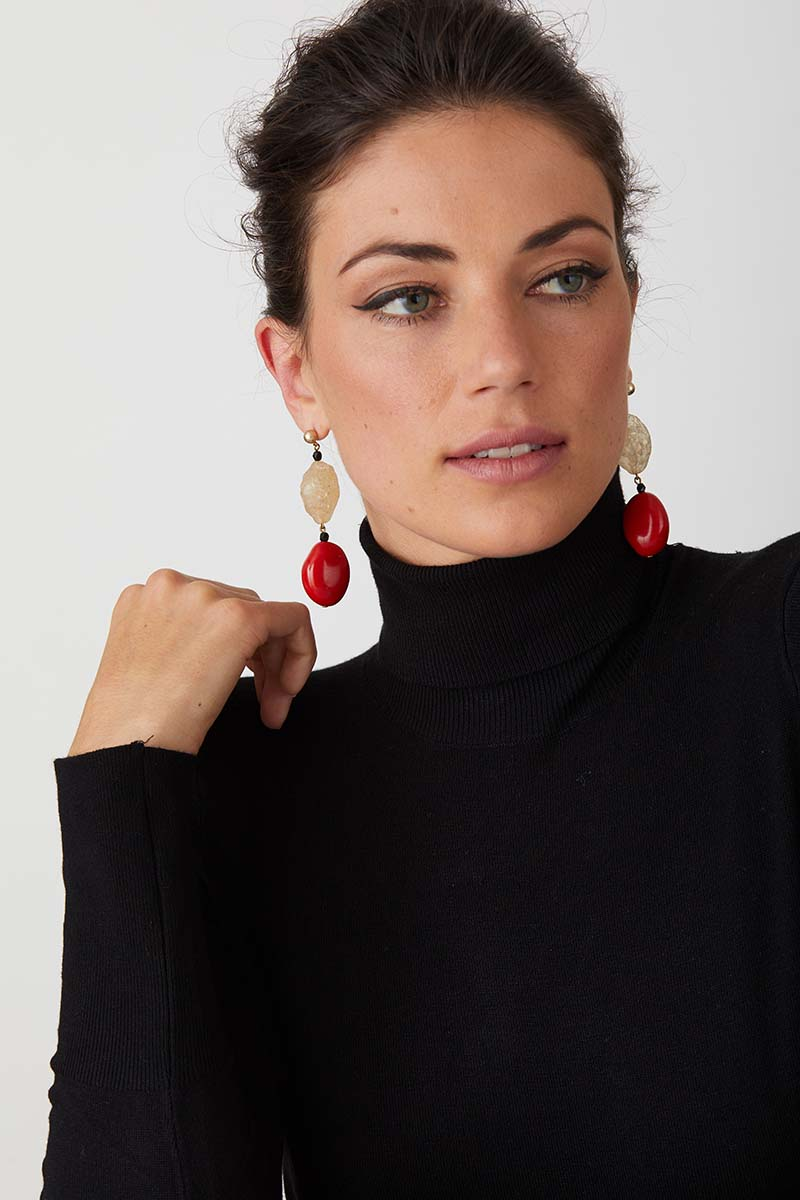 Red coral black statement earrings worn by a model in a black turtleneck