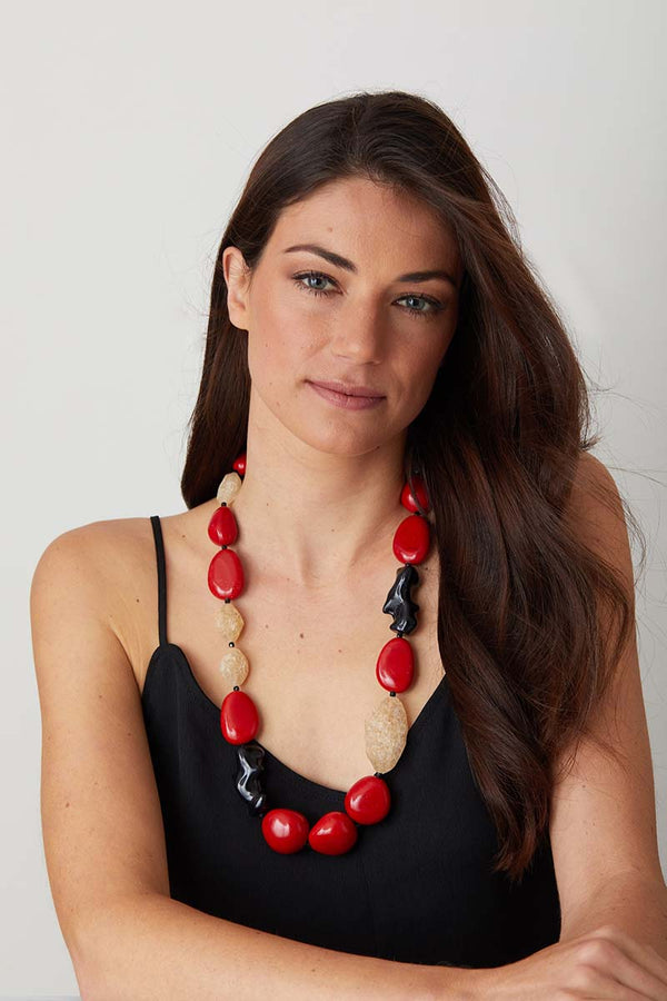 Red coral black statement necklace worn by a model in an elegant black dress