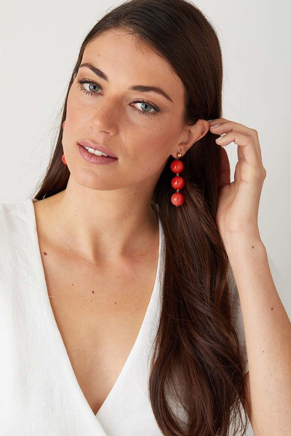 Orange coral statement earrings worn by a model in a  white summer top