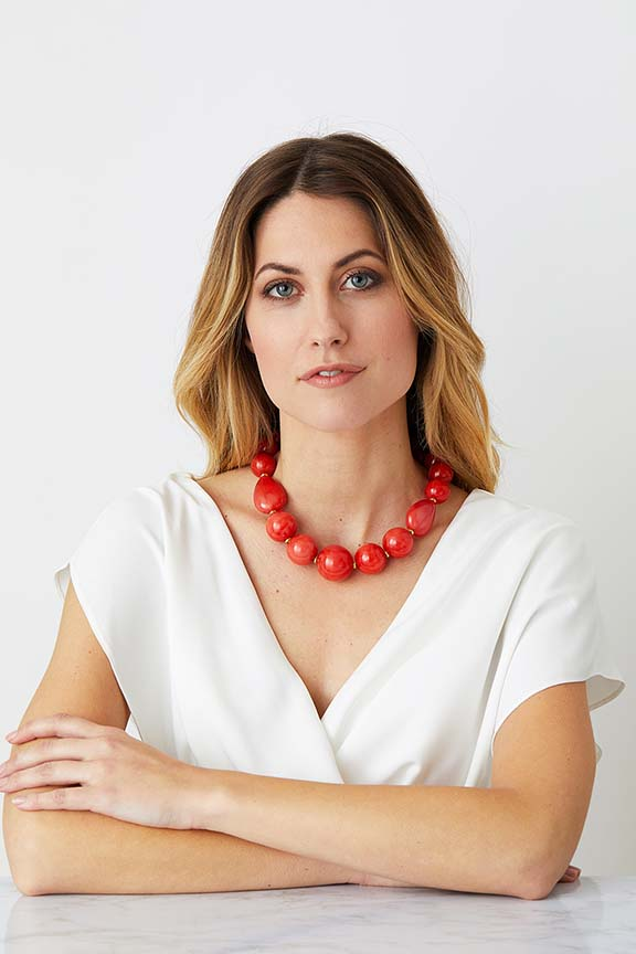 Orange coral gold statement necklace worn by a model in a white evening dress