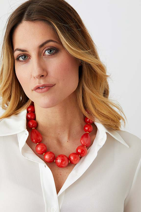 Orange coral gold statement necklace worn by a model in a white collared silk shirt