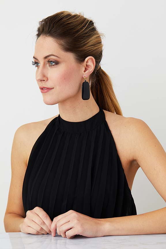 Black statement earrings worn by a model in a black evening elegant dress