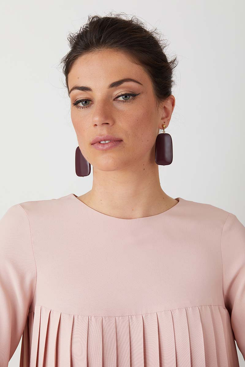 Burgandy statement earrings worn by a model in a pink pleated dress