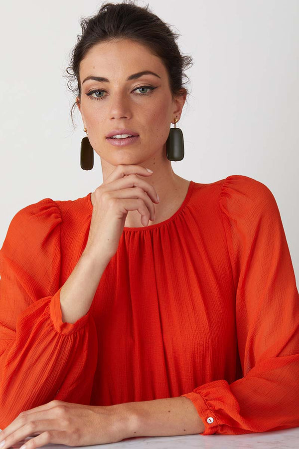 Green statement earrings worn by a model in a red summer dress