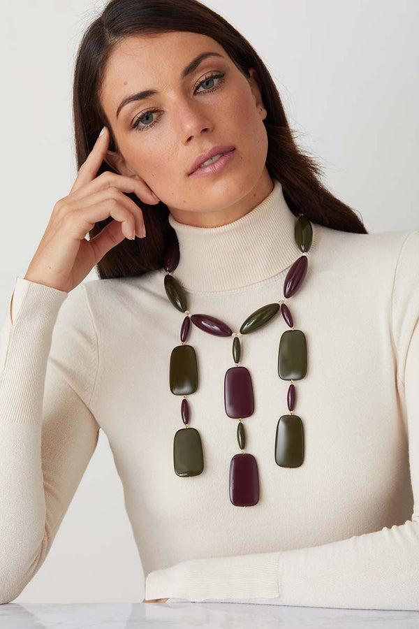 Green burgandy statement necklace worn by a model in a white turtleneck