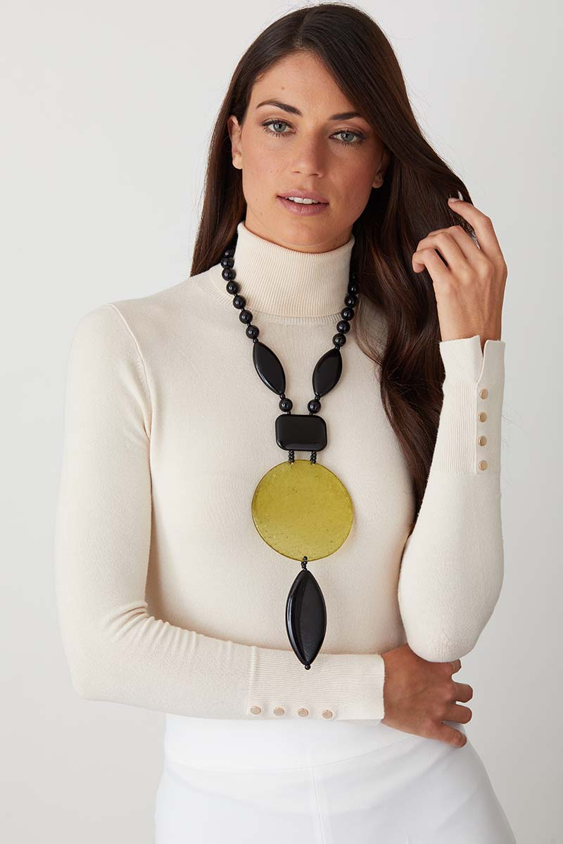 Black green statement necklace worn by a model in a white turtleneck
