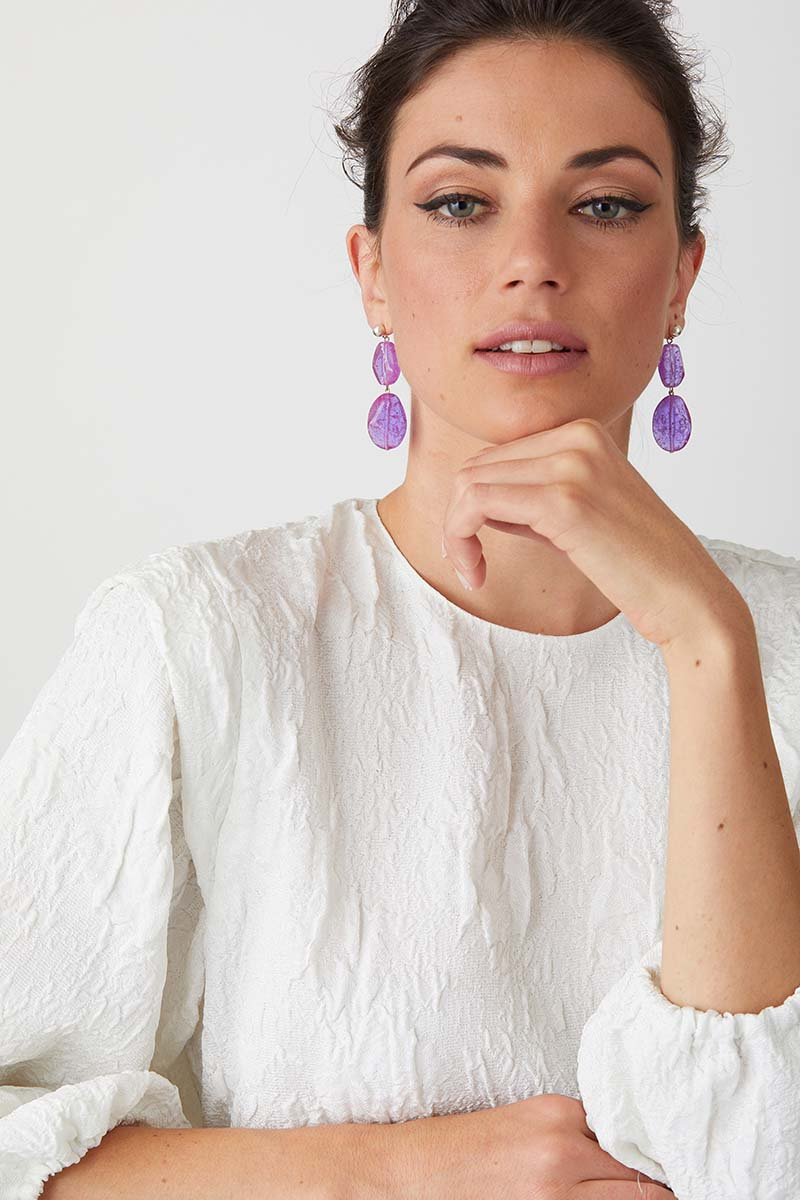 Purple statement earrings worn by a model in a white high fashion top