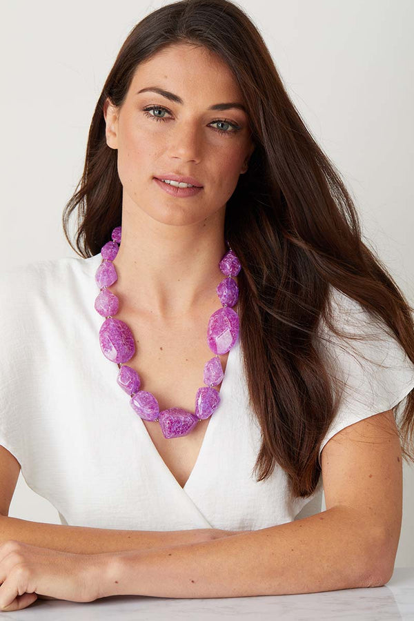 Purple resin statement necklace worn by a model in a white summer top