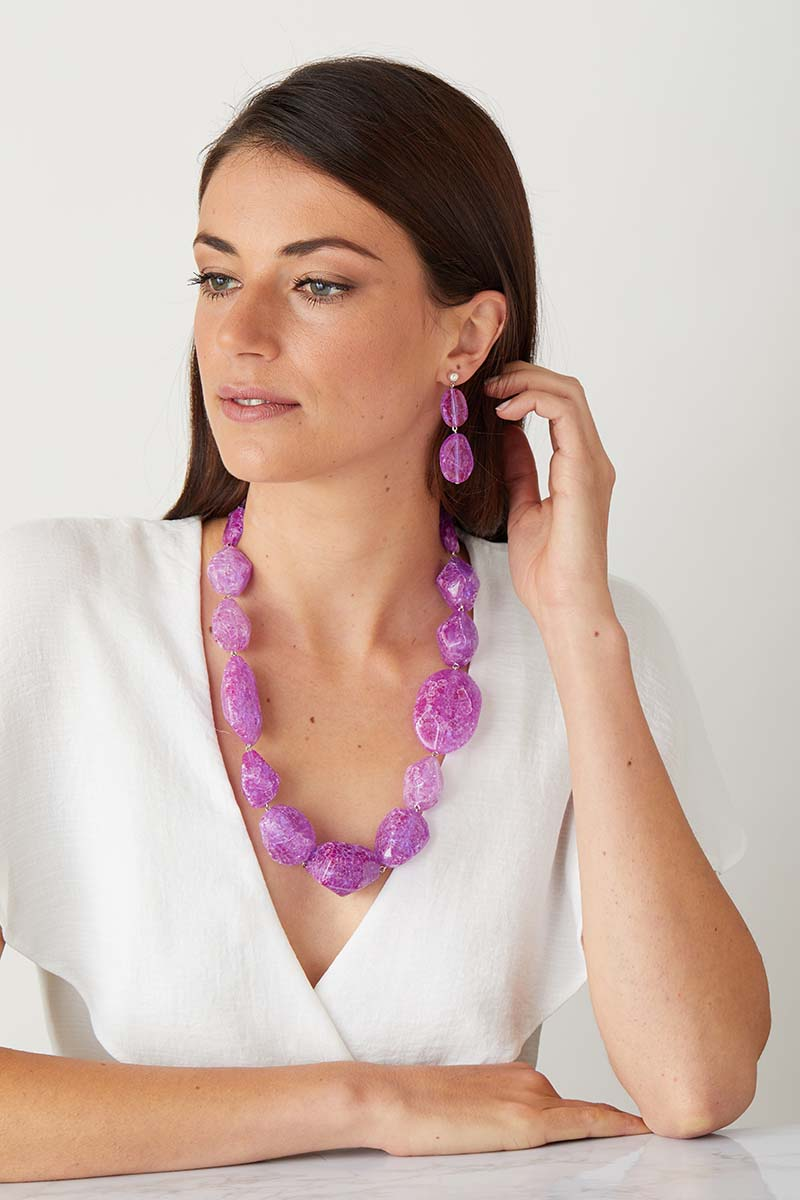 Purple statement earrings worn by a model as a pendant set