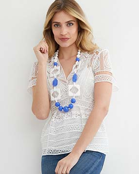 white blue long statement necklace worn by a model in a white lace shirt