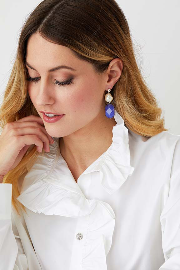 Baroque pearl blue statement earrings worn by a model in a ruffled collared white shirt