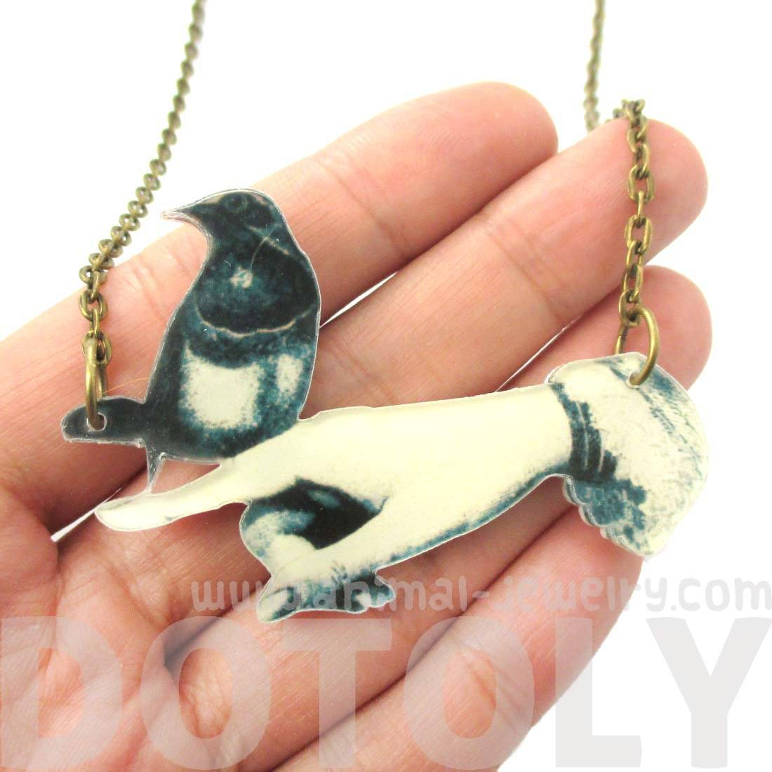 Bird Perched On A Hand Illustrated Vintage Pendant Necklace | DOTOLY