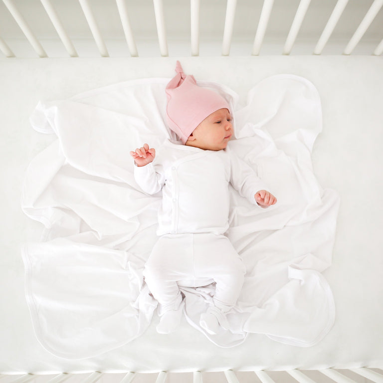 SNOW NEW BABY COMING HOME SET SHOWN ON BABY LAYING IN CRIB WITH A SNOW BASIC BLANKET AND SNOW BOOTIES, ALSO WEARING A LIGHT PINK KNOTTED BABY HAT. BABY IS LOOKING OFF TO THE SIDE