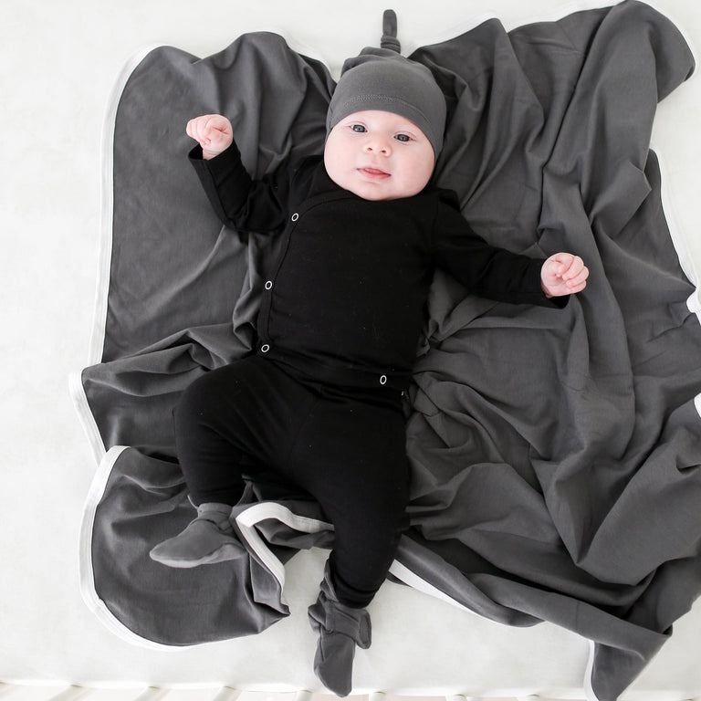 CHARCOAL FRESH BABY KNOTTED HAT SHOWN ON BABY LAYING IN CRIB WITH MATCHING CHARCOAL BASIC BLANKET AND BOOTIE SET, ALSO WEARING A BLACK COMING HOME SET LOOKING AT THE CAMERA