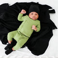 Thumbnail for baby shown wearing the onyx fresh baby knotted hat, laying on an onyx blanket and wearing a green coming home outfit and onyx booties, baby is looking into the camera